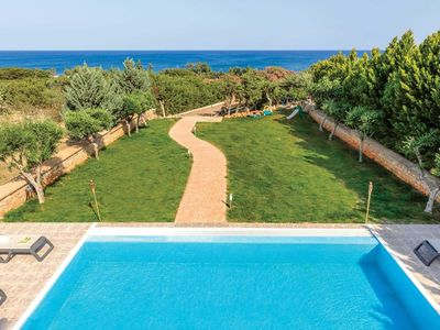 Photo for Sandy Gennadi beach is directly in front the villa with the lovely swimming pool and lawns, stunning sea views, beach bars within walking distance, a smart modern villa with table tennis and barbecue, this villa has it all!