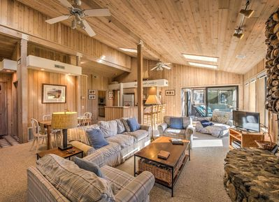 Modern rustic living room with plaid couches and stone fireplace