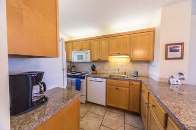 Fully equipped kitchen with new dishwasher, stove, sink and microwave above.