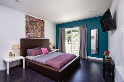 """Master bedroom with top of the line bed and bedding, 45""""TV and sliding doors out"""