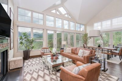 Huge panel of windows in this beautifully appointed living space perfectly frames the mountains beyond