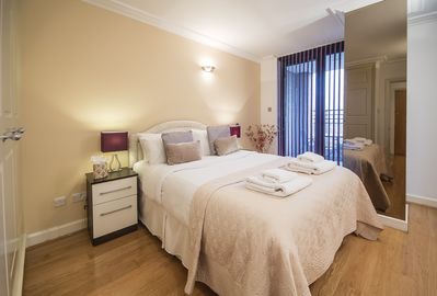 This master bedroom offers a king-size bed, a large set of fitted wardrobes and