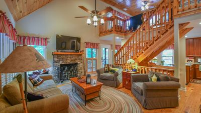 First floor Den with Stack Stone fireplace, large TV and relaxing chairs