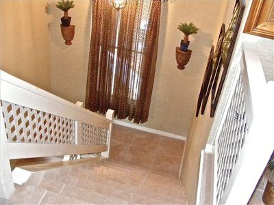 Tiled Stairs Leading To Upstairs Villa With Golf, Lagoon, and Wooded Views.