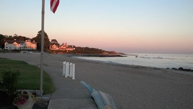 Sandy beach at sunset looking toward rock outcropping