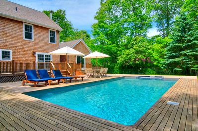 Heated pool surrounded by mahogany decking and expansive yard