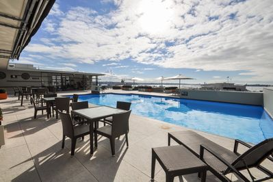 Play: Shared rooftop pool/terrace/gym with harbour views