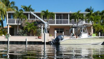 Back of home, featuring 70' dock, screen porch upstairs, tiki hut w/dining area