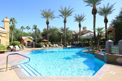 Resort style heated pool with lounges, umbrellas, covered gazebo and gas grills