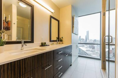 Bathroom features a walk in shower and beautiful city views