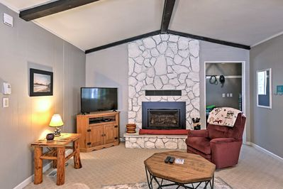 The stone gas fireplace and gorgeous wood beams highlight the living space.