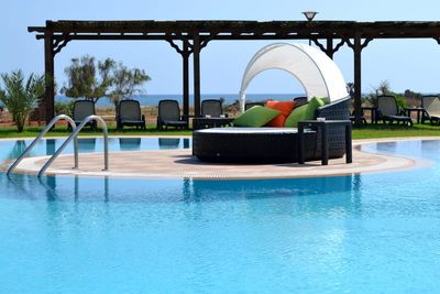 Large freeform pool with plenty of sunloungers, cabanas and other seating.