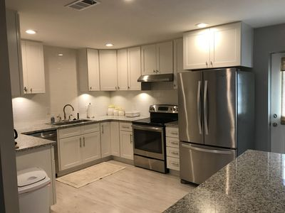 Fully stocked kitchen with stainless appliances.