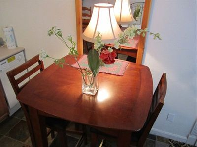Table with two, high back bar stools. Utensils in the table drawer. Dishwasher