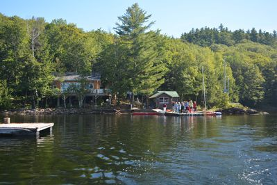 The view of the cottage and boathouse from the lake, and  the family on the dock