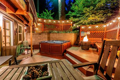 Relax in back patio with hot tub, fire ring, and  patio lighting