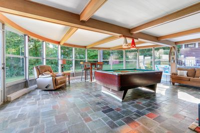 The 3 season sun room is a round glass room with a pool table.