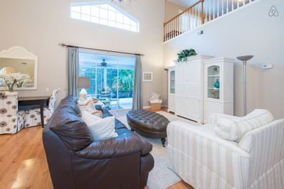 Spacious family room, TV inside white hutch. Triple sliding doors to open patio.