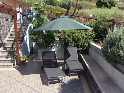 Large , sunny  terrace with sun beds and umbrella
