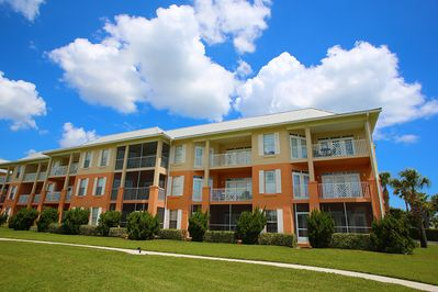 Well-maintained condo building with grassy areas for playing ball