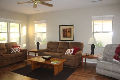 Living room has dual reclining sofas, comfortable recliner and ceiling fan