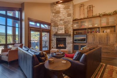 Living Room - Floor to ceiling windows, incredible views,  plenty of seating, queen sofa sleeper, large fireplace, TV, DVD and two cozy chairs by the windows