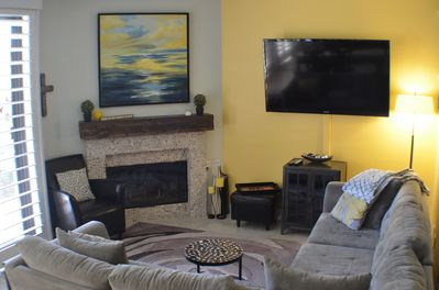living area features sectional couch, gas fireplace, and large flat screen TV