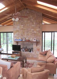 Living Rm with local pink beige brown and red limestone, fireplace is never used