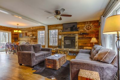 Living room with beautiful wood burning fireplace which is open to the kitchen