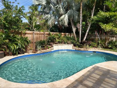 Tropical escape with lush landscaping, waterfall, and water jets for the kids