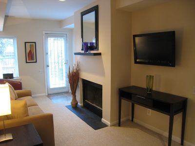 Second entrance, HDTV. - Seating for 4 guests faces fireplace and wall mounted HDTV. Sofa folds out to a double bed. Door leads to your private patio with outdoor dining for 4.