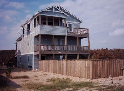 Back of the house that faces the ocean with hot tub on second level