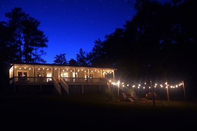 Lakeside view of The Cottage at dark. Enjoy the vintage lighting and firepit.