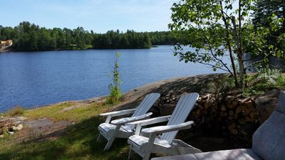 View of the lake including muskoka chairs