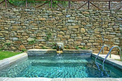 Small stone swimming-pool provided with hydromassage jets and  waterfall