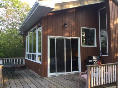 Front deck with covered porch over Broil King barbecue, hot tub, and huge door and windows