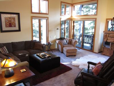Cozy and bright family room with fireplace, BBQ deck, and TV.