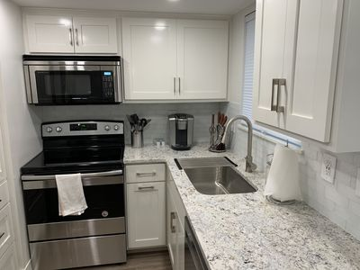 Modern Kitchen with white ice granite countertops, glass tile backsplash, soft close custom cabinets, pull out trash can, kitchen aid dishwasher, sharp convection microwave, keurig k-elite,  Amana smooth top range, and recessed led lighting.