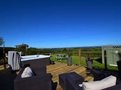 The hot tub which boast spectacular views across the rolling Devonshire countryside