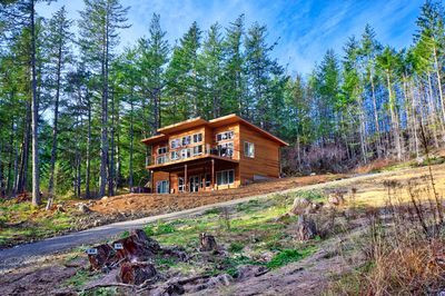 Northwest Modern design with cedar siding, perched on the hillside.