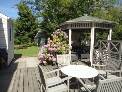 Fully fenced in garden with mature trees, deck and gazebo.
