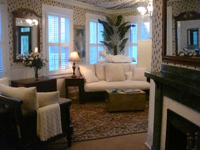 The spacious living room features a tented ceiling, British Colonial style furnishings and two fireplaces.