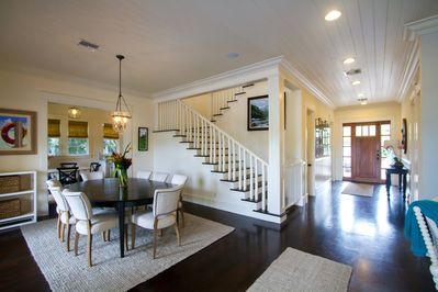 The view of the front door, stair case, dining room and kitchen in the back