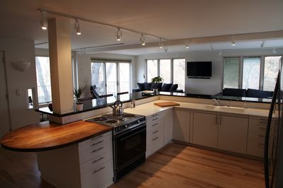 Large, social kitchen with vintage stove, stainless fridge and dishwasher.