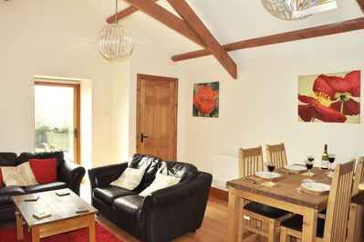 Ground floor: Spacious open plan sitting room with high pitched ceiling