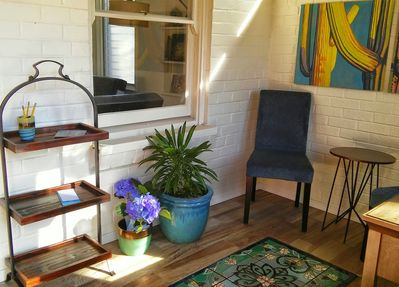 Enjoy coffee in the bright entry room featuring tiles and painting by local arti