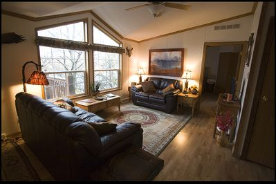 Living room with large deck outside and view through the trees to the lake.