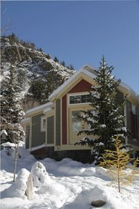 Side of cottage in winter, with mountain and hiking trails in the background.