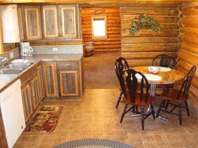 The lovely eat-in kitchen has dining for 4 & custom cabinets made by the owner.