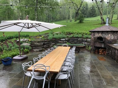 16 foot table seats up to 20 . Patio features Pizza Oven, Charcoal, & Gas Grill.
